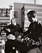 GREECE, Patmos, Skala, Dodecanese Island, taverna owner and musician Yannis Kaneli and Kiriakos play music at his restaurant, Taverna Tzivaeri (B&W)