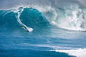 USA, Hawaii, Maui, a man windsurfs on huge waves at a break called Jaws or Peahi