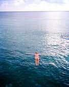 HONDURAS, Roatan, woman floating on sea surface