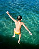 HONDURAS, Roatan, boy jumping into the Caribbean Sea