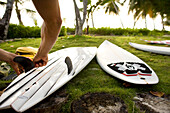 INDONESIA, Mentawai Islands, Kandui Surf Resort, a person putting fins on his surfboards
