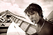 INDONESIA, Mentawai Islands, Kandui Surf Resort, young surfer with sunscreen on his face, smoking and holding a surfboard (B&W)