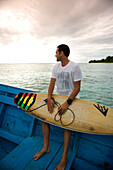 INDONESIA, Mentawai Islands, Kandui Surf Resort, young man sitting on boat with surfboard