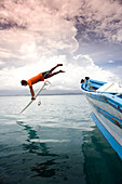 INDONESIA, Mentawai Islands, Kandui Surf Resort, surfer diving into the Indian Ocean with his surfboard