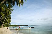 INDONESIA, Mentawai Islands, Kandui Surf Resort, surfers loading a boat to go surfing