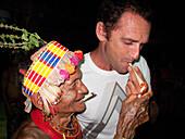 INDONESIA, Mentawai Islands, Kandui Resort, Mentawaian man lighting hand rolled cigarettes.