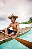 INDONESIA, Mentawai Islands, Kandui Resort, fisherman Gesayas Ges paddling his dugout canoe