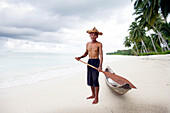 Indonesia, portrait of senior man holding oar by canoe at beach
