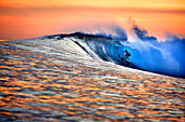 INDONESIA, Mentawai Islands, Kandui Resort, man surfing on wave at dusk, Bankvaults