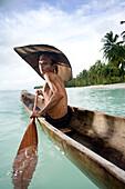 INDONESIA, Mentawai Islands, Kandui Resort, portrait of a Mentawai fisherman, Gesayas Ges, in his dugout canoe