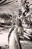 INDONESIA, Mentawai Islands, Kandui Resort, portrait of smiling senior woman holding surfboard (B&W)