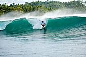 INDONESIA, Mentawai Islands, Kandui Resort, man surfing a wave called Beng Beng