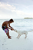 INDONESIA, Mentawai Islands, Kandui Resort, young man wrestling a coconut from a dog's mouth on the beach