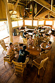 INDONESIA, Mentawai Islands, Kandui Resort, people having breakfast in a dining lodge