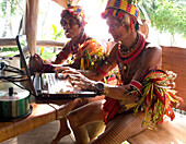 INDONESIA, Mentawai Islands, Kandui Resort, tribal senior tribal man pretending to use a laptop