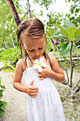 INDONESIA, Mentawai Islands, Kandui Resort, young girl holding a plumeria flower, looking down