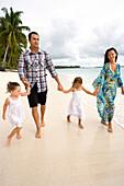 INDONESIA, Mentawai Islands, Kandui Resort, family walking on the beach