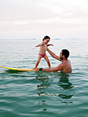 INDONESIA, Mentawai Islands, Kandui Resort, father helping daughter stand on a surfboard