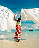 MADAGASCAR, woman hanging tapestries at Jardin Vanille Beach, Nosy Be
