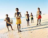 MADAGASCAR, boys holding toy handmade boats at beach, Anjajavy