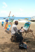 MAURITIUS, an artist creates and sells his paintings by the water in Trou du D'eau