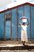 MAURITIUS, Bois Cherie, Mutty Megah (age 63) stands in front of her house before walking to a small stream behind her home to wash clothes