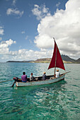 MAURITIUS, Trou D'eau Deuce, sailors on the East coast of Mauritius with the 4 Sisters Mountains in the background, Indian Ocean