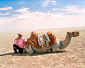 MONGOLIA, Nemegt Basinmid, adult man takes a rest with his camel and smokes, The Gobi Desert