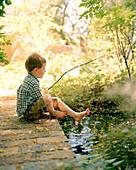 USA, New Mexico, boy holding stick, sitting by pond, Los Poblanos Inn, Alburquerque