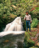 PANAMA, David, Guadalupe, Los Quetzales Lodge, a local Chiriqui guide and birder stands by a beautiful waterfall in the cloud forest