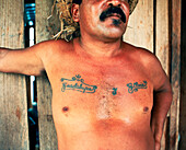 PANAMA, Bocas del Toro, a local man is tattooed with the names of his mother and wife, Central America