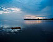 PANAMA, Bocas del Toro, a fisherman drives his boat in the earl morning dawn, Central America