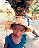 PANAMA, Bocas del Toro, a young boy Tapio finds shade under a fallen tree trunk, Central America