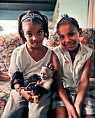 PANAMA, Bocas del Toro, portrait young girls hold a pet monkey in their home, Central America