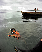 PANAMA, Bocas del Toro, a man freedives and comes to the surface with a crab, his son holds up a fish and a lobster, the Caribbean Sea off the coast of Isla Colon, Central America