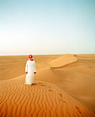 SAUDI ARABIA,The Empty Quarter, Najran, teenage boy standing on sand dune