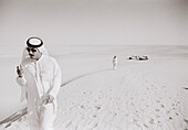SAUDI ARABIA, man wearing a traditional Thobe and smoking in The Empty Quarter, Najran (B&W)