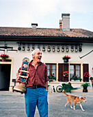 SWITZERLAND, Motiers, George Montandon stands in front of his home holding a cow bell that was given to him by a friend for his 45th wedding anniversary, Jura Region