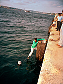 TURKEY, Istanbul, a man tries to reach out from a pier to retrieve his soccer ball, the Sea of Marmara