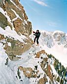 USA, Utah, skier climbing around rocky cliff, holding onto a rope, High Sunspot, Alta Ski Resort