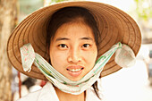 VIETNAM, Hanoi, portrait of a beautiful young woman selling produce and wears a non la or leaf hat, the old quarter of town