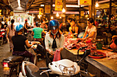 VIETNAM, Hanoi, a young woman buys meat from a butcher in the Chau Long Market