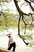 VIETNAM, Hanoi, a woman performs Tai Chi and stretches early in the morning, Hoan Kiem Lake