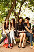 VIETNAM, Hanoi, young women sitting together on a bench by Hoan Kiem Lake