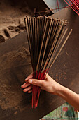 VIETNAM, Hue, a woman holds incense that she recently rolled and is selling on the roadside