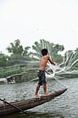VIETNAM, Hue, Perfume river, fisherman Tran Van Son casting his fishing net from the bow of his Sampan boat, La Y Village, Phu Vang District, Thua Thien Hue Province