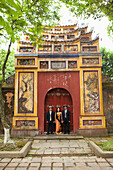 VIETNAM, Hue, a woman stands with her husband and brother in law by a large painted gate in the Citadel