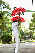 VIETNAM, Saigon, Ho Chi Minh City, woman exercise and perform perfect movements with fans in the early morning