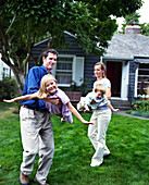 USA, Washington State, Seattle, a family plays in the front yard of their house