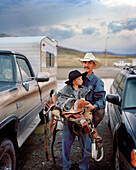 USA, Wyoming, portrait of Saddle Bronc Cowboy carrying his son and saddle, Cody Rodeo